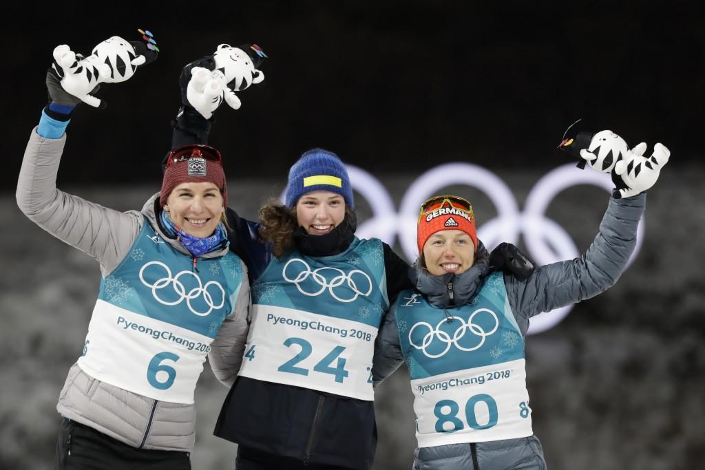 Silver medalist Anastasiya Kuzmina, of Slovakia, left, gold medalist Hanna Oeberg, of Sweden, center and bronze medalist Laura Dahlmeier, of Germany,