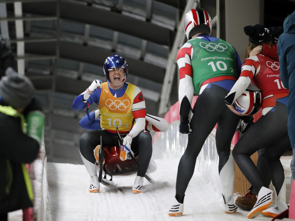 Summer Britcher, in red, Chris Mazdzer, in green, Matt Mortensen and JaysonTerdiman of the United States react in the finish area after the luge team