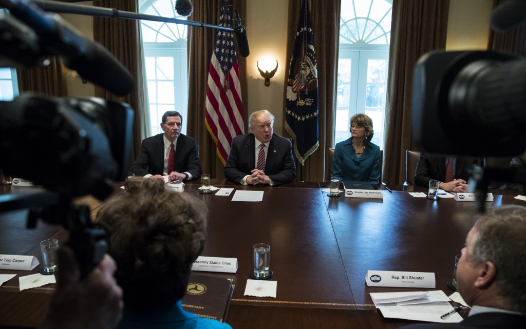 President Donald Trump, joined by Sen. John Barrasso, R-Wyo., left, and Sen. Lisa Murkowski, R-Alaska, right, speaks to media during a meeting with bi