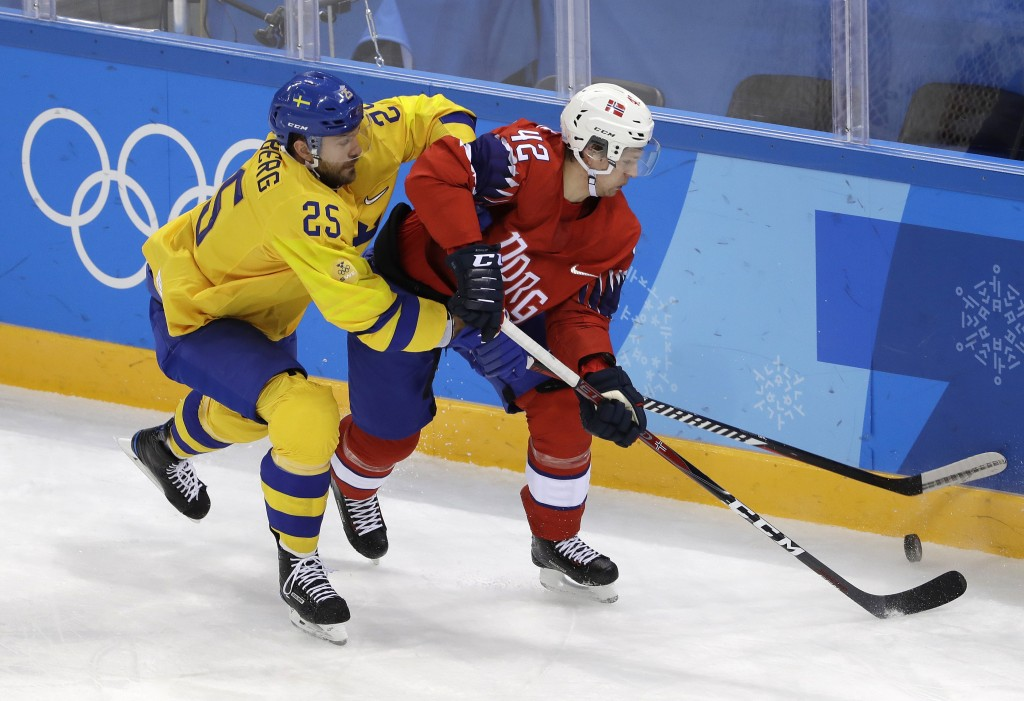 Viktor Stalberg (25), of Sweden, and Henrik Odegaard (42), of Norway, battle for the puck during the first period of the preliminary round of the men'