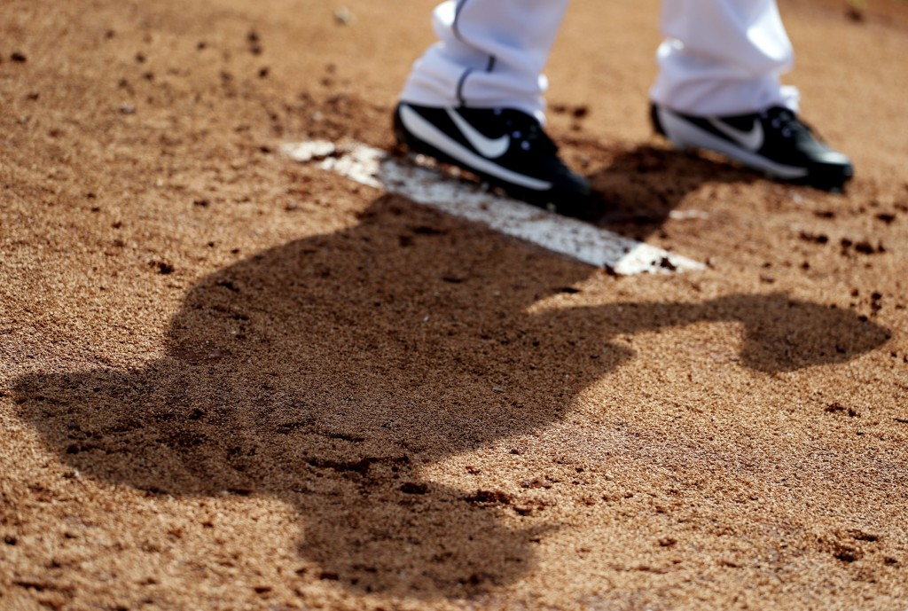 The shadow of Miami Marlins pitcher Javy Guerra in seen on the ground as he throws in the bullpen during spring training baseball practice Wednesday,