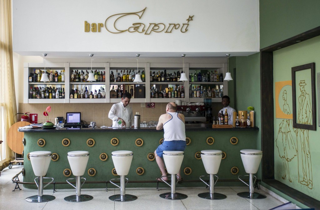 FILE - In this Sept. 12, 2017, file photo, a customer sits at the lobby bar of the Hotel Capri in Havana, Cuba. Doctors are releasing the first detail