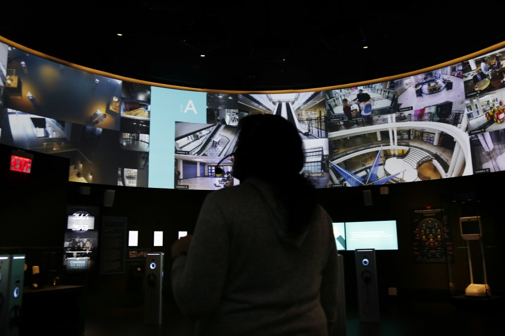 In this Monday, Feb. 12, 2018 photo, a reporter tries out an interactive surveillance exhibit at SPYSCAPE in New York. Visitors to a new attraction op