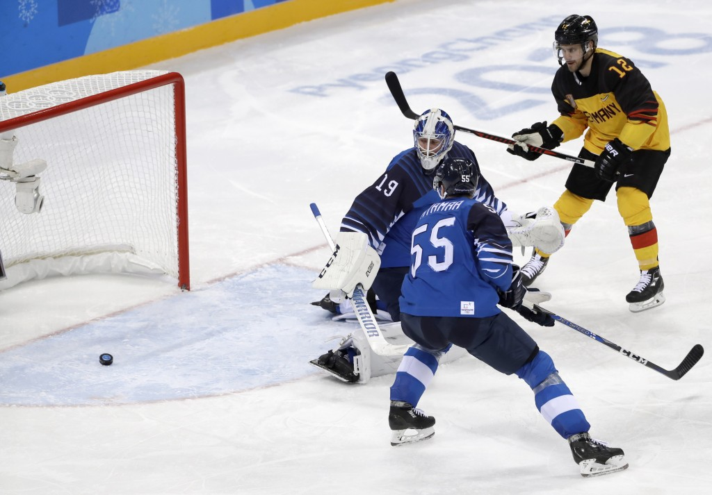 The puck shot by Frank Hordler, of Germany, sails past goalie Mikko Koskinen (19), of Finland, during the third period of the preliminary round of the