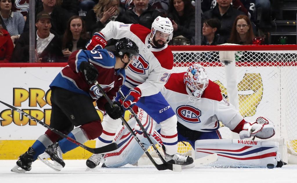 Colorado Avalanche left wing Gabriel Bourque, front, is blocked by Montreal Canadiens defenseman David Schlemko, center, as goaltender Antti Niemi sto