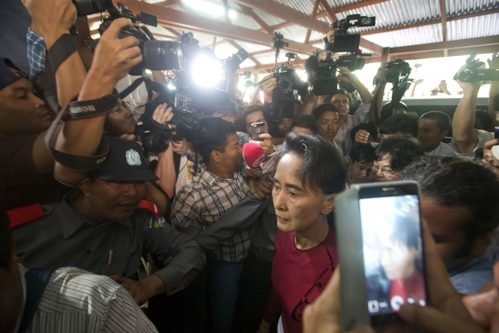 FILE - In this Nov. 8, 2015 file photo, Myanmar's National League for Democracy party leader Aung San Suu Kyi is crushed by the media as she arrives a