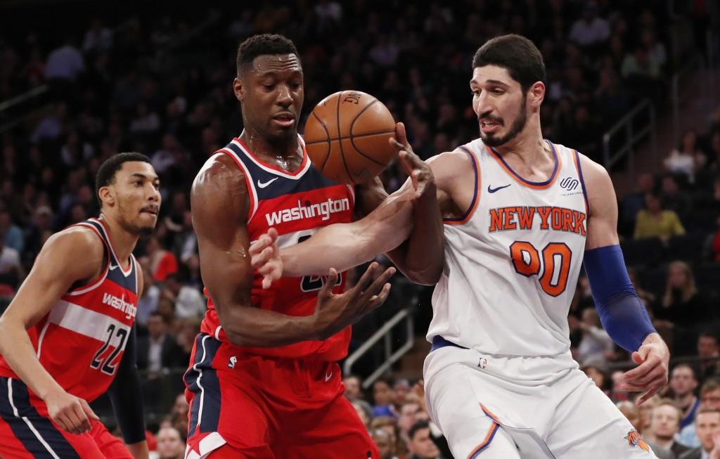 New York Knicks center Enes Kanter (00) loses the ball to Washington Wizards center Ian Mahinmi, center, as Washington Wizards forward Otto Porter Jr.