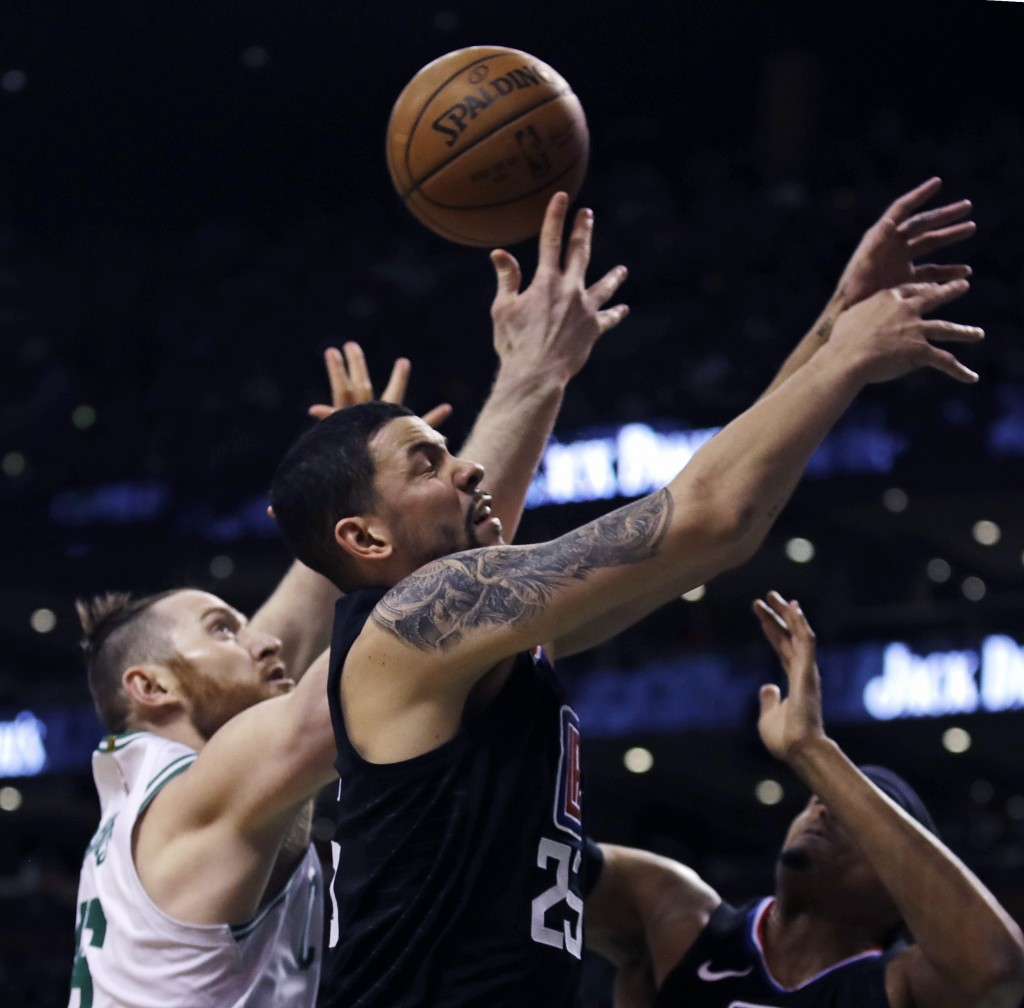 Los Angeles Clippers guard Austin Rivers (25) and Boston Celtics center Aron Baynes, left, vie for a rebound during the first quarter of an NBA basket