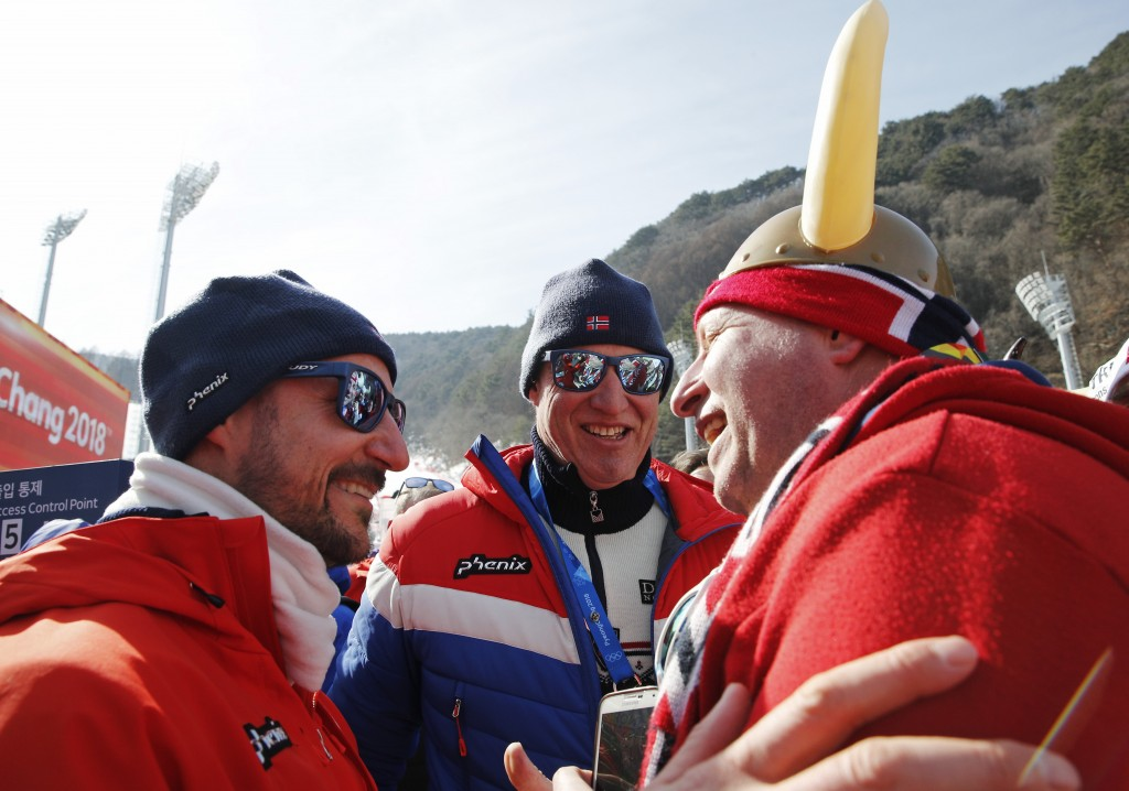 Crown Prince Haakon of Norway, left, greets fans at the men's downhill at the 2018 Winter Olympics in Jeongseon, South Korea, Thursday, Feb. 15, 2018.