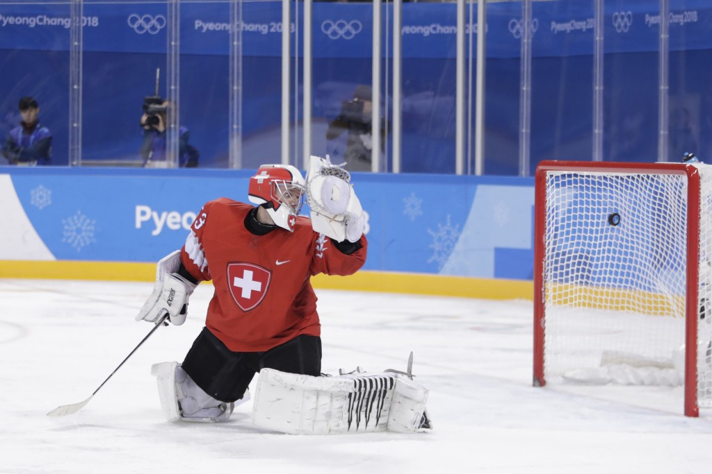 Switzerland goalkeeper Leonardo Genoni watches as a shot by Wojtek Wolski (8), of Canada, enters his net for a goal during the second period of a prel