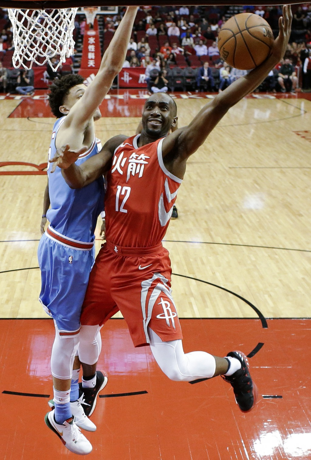 Houston Rockets forward Luc Mbah a Moute drives to the basket as Sacramento Kings forward Justin Jackson defends during the first half of an NBA baske