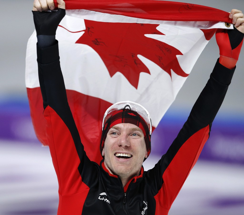 Gold medallist Ted-Jan Bloemen of Canada celebrates with the national flag after the men's 10,000 meters speedskating race at the Gangneung Oval at th