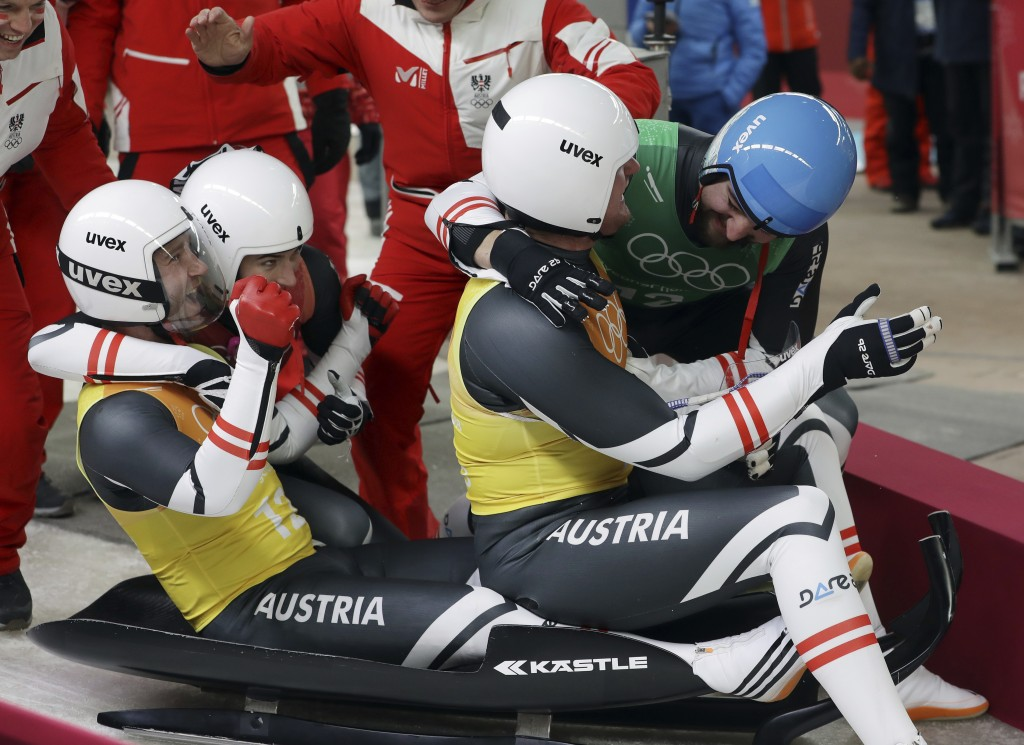 Madeleine Egle, in red, David Gleirscher, in green, Peter Penz and Georg Fischler of Austria react in the finish area after winning the bronze medal i