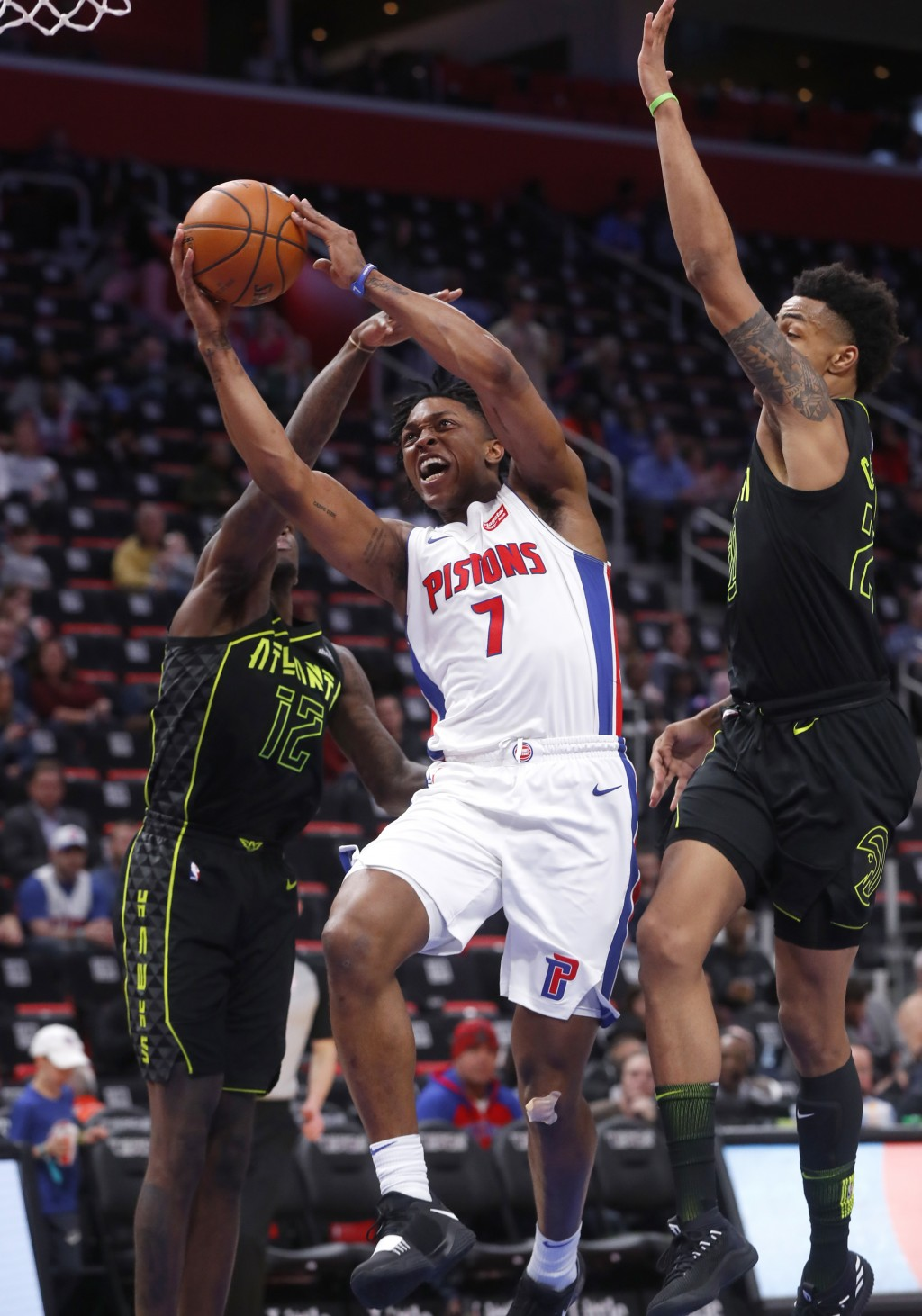 Detroit Pistons forward Stanley Johnson (7) drives between Atlanta Hawks forward Taurean Prince (12) and Atlanta Hawks forward John Collins in the sec