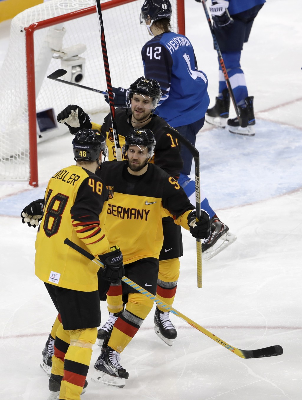 Frank Hordler (48), of Germany, celebrates a goal against Finland with his teammates during the third period of the preliminary round of the men's hoc