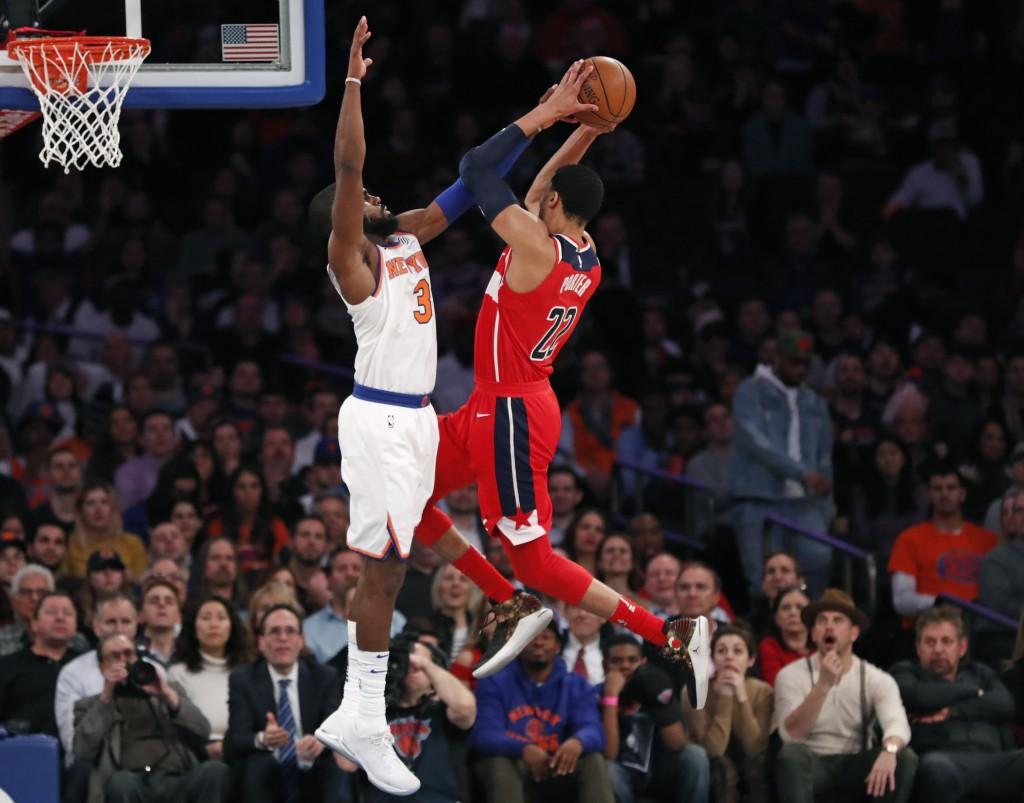 New York Knicks forward Tim Hardaway Jr. (3) fouls Washington Wizards forward Otto Porter Jr. (22) in the second half of an NBA basketball game in New
