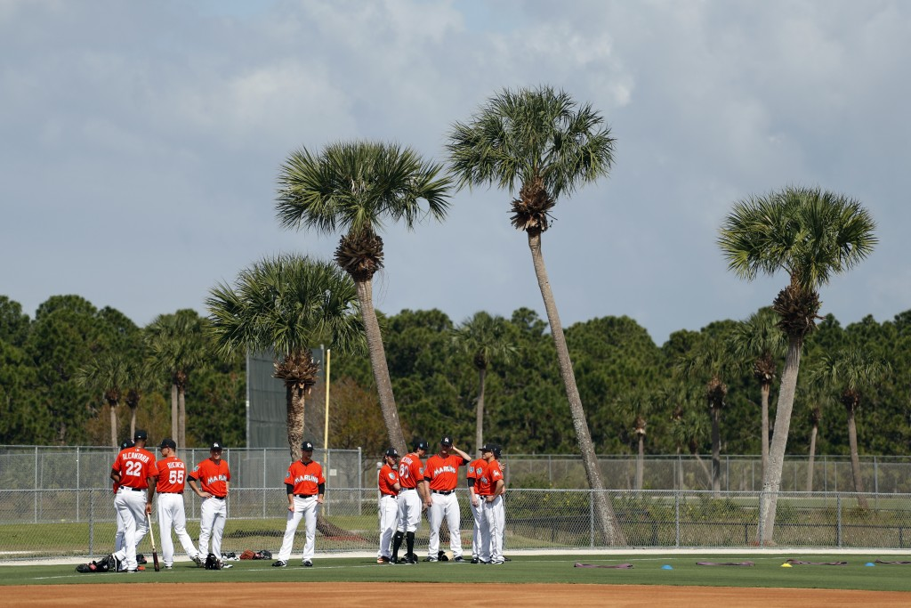 Members of the Miami Marlins pause before stretching during spring training baseball practice Wednesday, Feb. 14, 2018, in Jupiter, Fla. (AP Photo/Jef