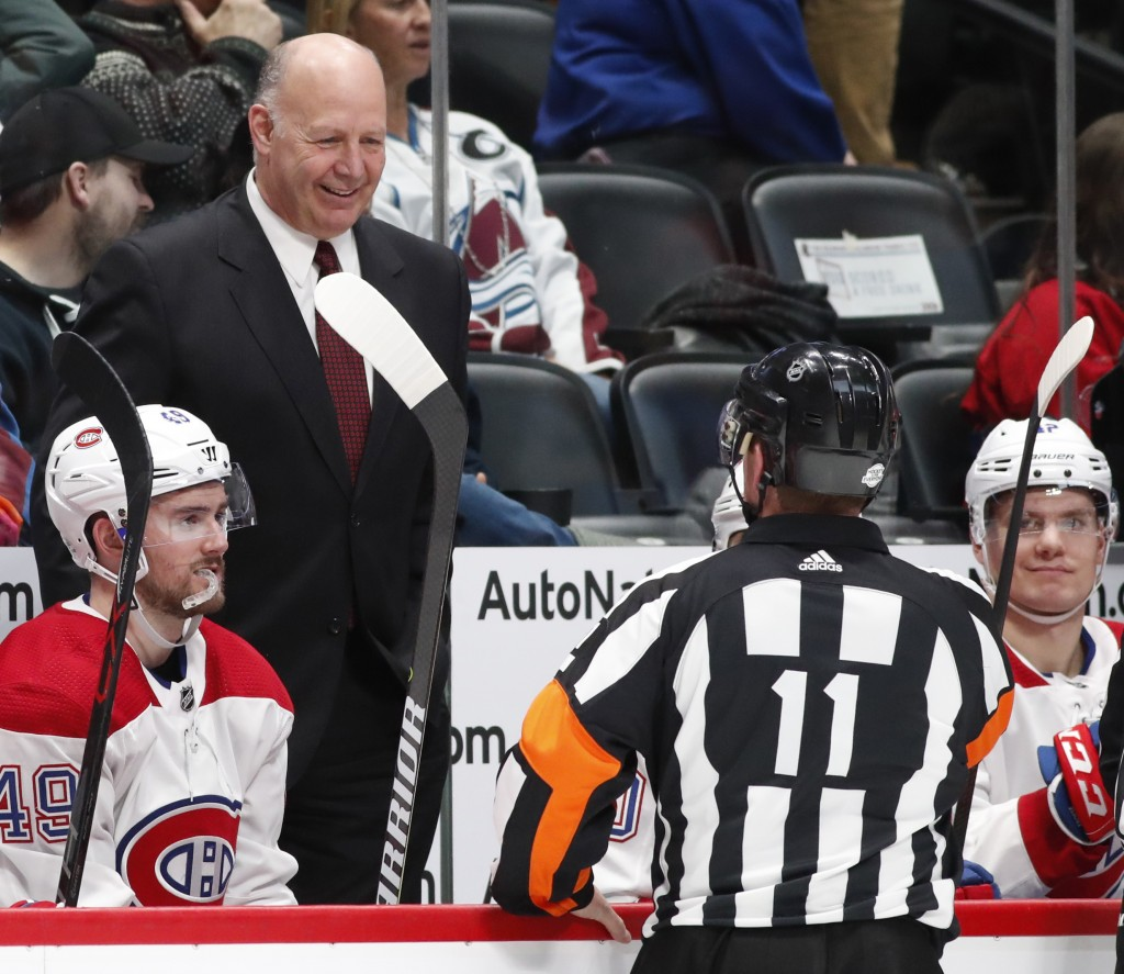 Montreal Canadiens head coach Claude Julien, left, confers with referee Kelly Sutherland in the second period of an NHL hockey game against the Colora