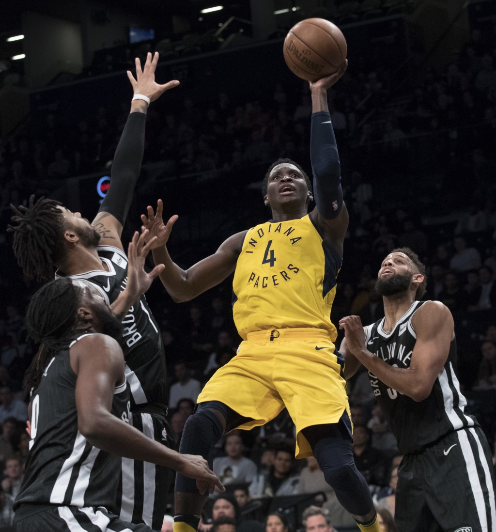 Indiana Pacers guard Victor Oladipo (4) goes to the basket past Brooklyn Nets forward DeMarre Carroll, left, guard D'Angelo Russell, second from left,