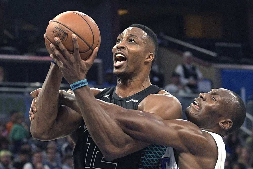 Charlotte Hornets center Dwight Howard (12) is fouled by Orlando Magic center Bismack Biyombo, right, while going up for a shot during the first half