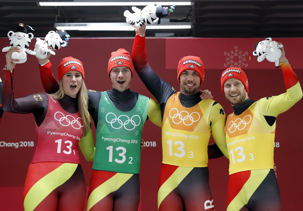 From left, Natalie Geisenberger, Johannes Ludwig, Tobias Wendl and Tobias Arlt of Germany celebrates winning the gold medal in the finish area after t