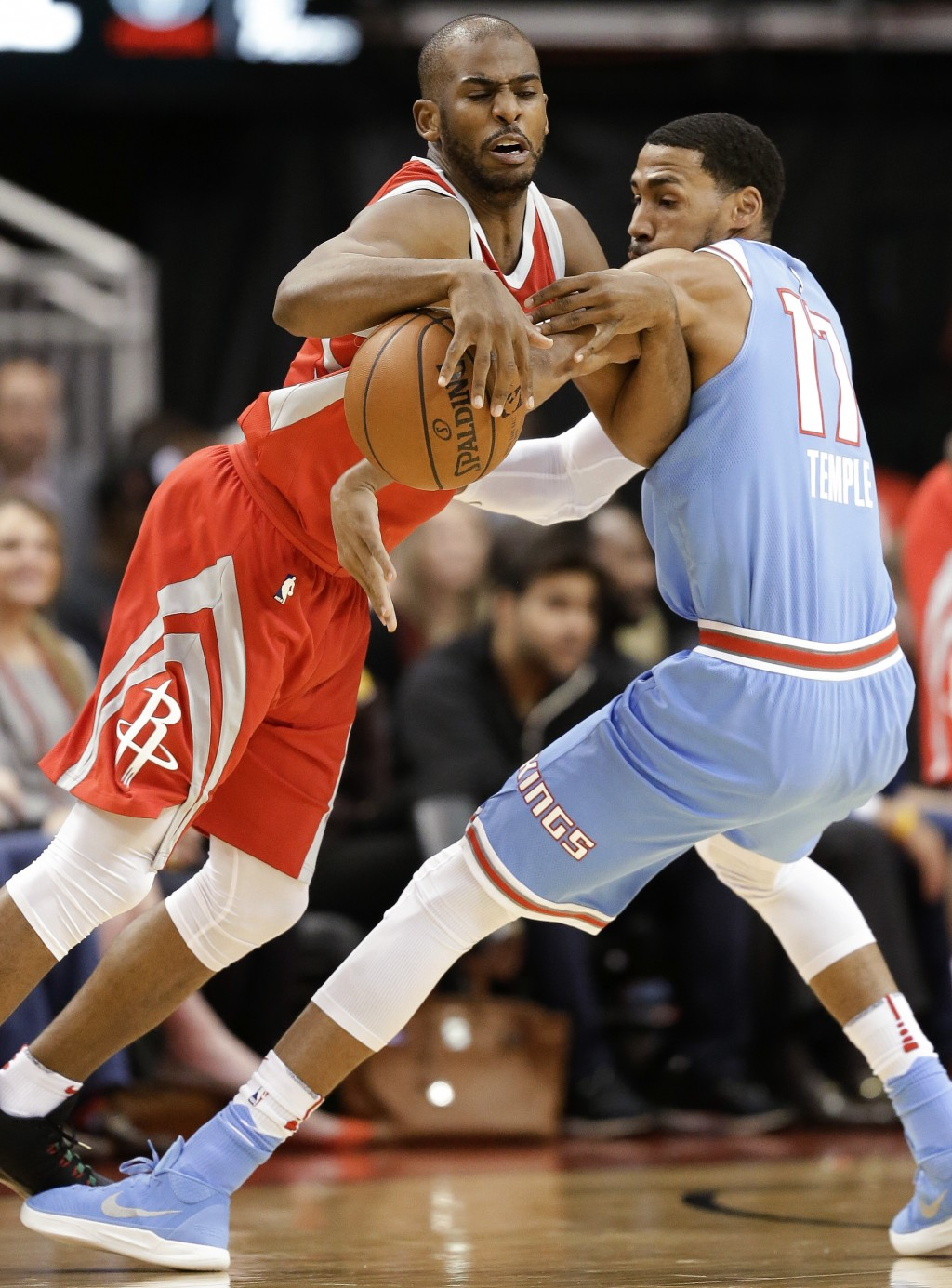 Houston Rockets guard Chris Paul, left, is fouled by Sacramento Kings guard Garrett Temple during the first half of an NBA basketball game Wednesday,