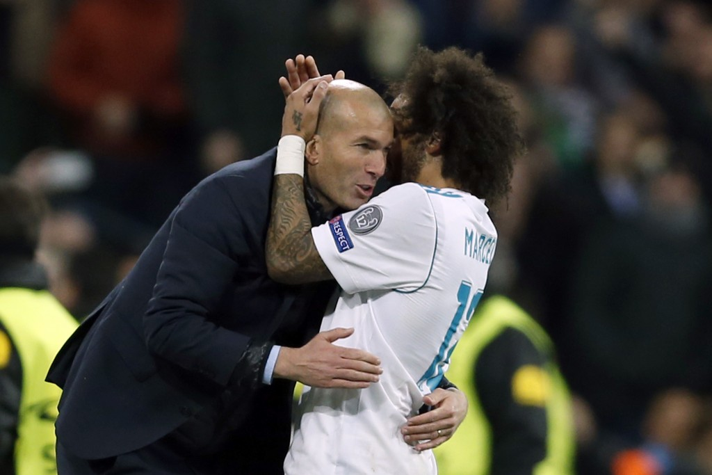 Real Madrid's Marcelo celebrates his side's 3rd goal with his head coach Zinedine Zidane during a Champions League Round of 16 first leg soccer match
