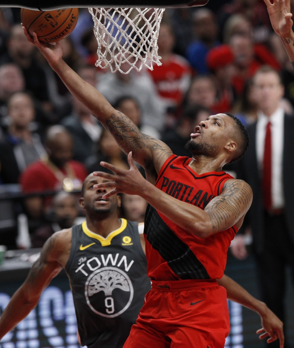 Portland Trail Blazers guard Damian Lillard, right, drives past Golden State Warriors forward Andre Iguodala during the first half of an NBA basketbal