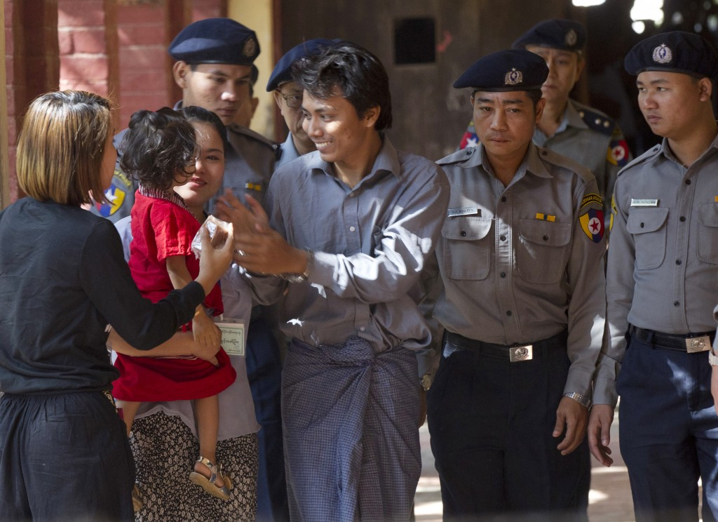 FILE - In this Feb. 1, 2018, file photo, Reuters journalist Kyaw Soe Oo, centre, is welcomed by his wife and daughter upon arrival at the court for th