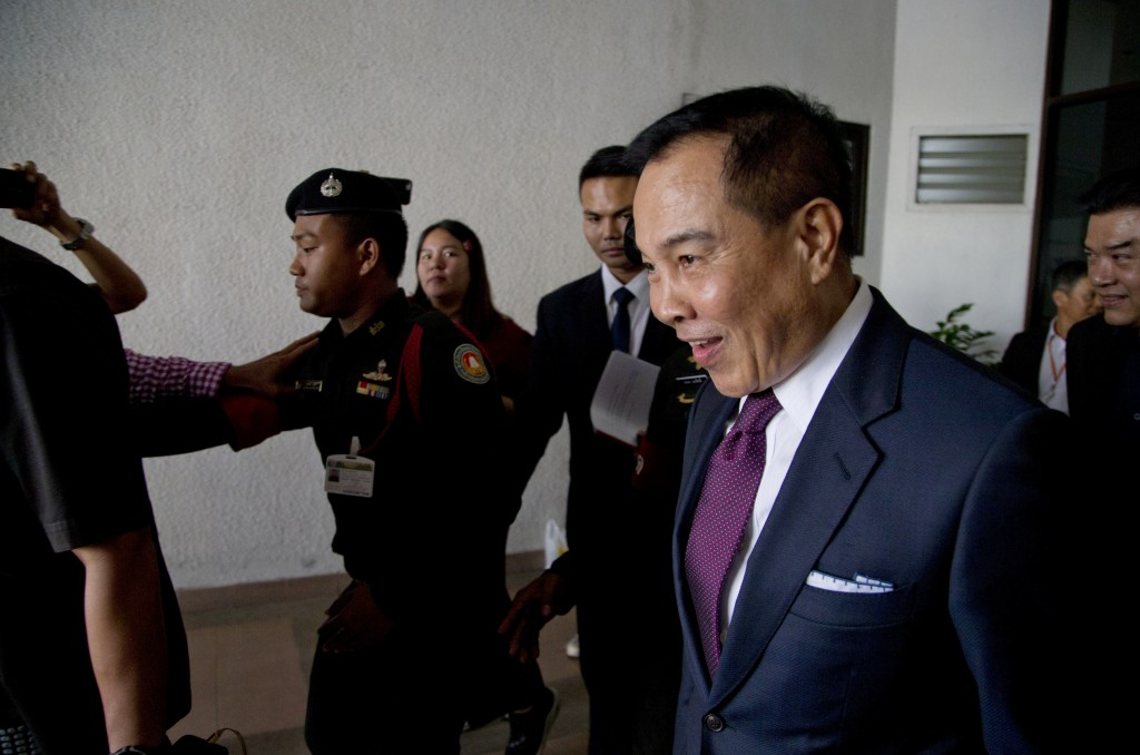Thai former national police chief Somyot Poompanmoung, right, leaves after being interrogated at Department of Special Investigation in Bangkok, Thail