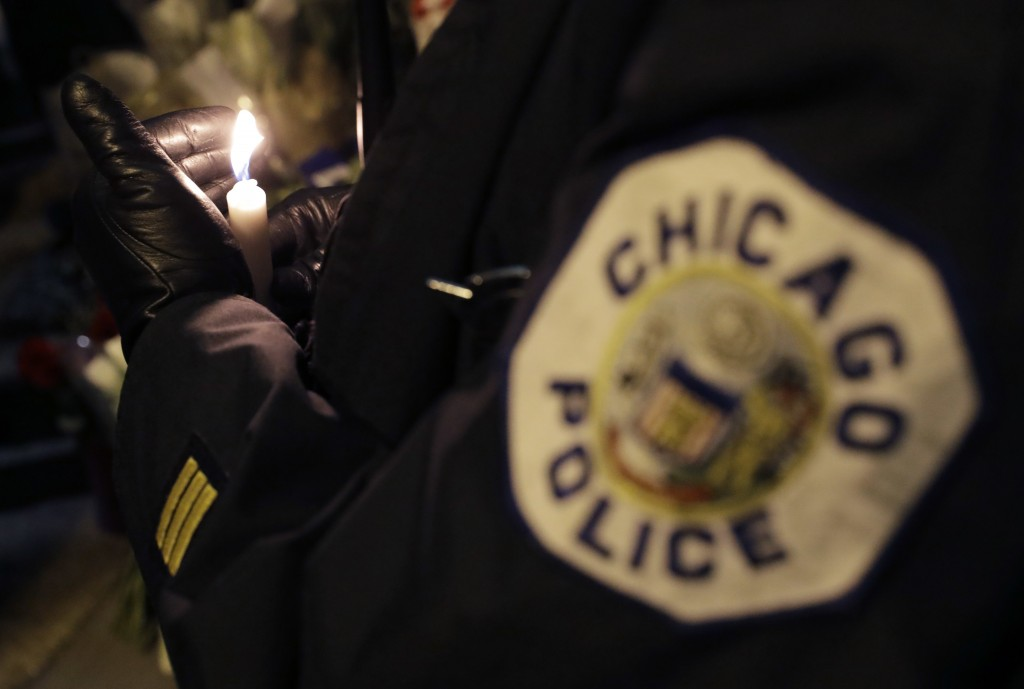 A Chicago police officer shields their candle from the wind as they attend a candlelight vigil for police Cmdr. Paul Bauer outside the Near North Dist