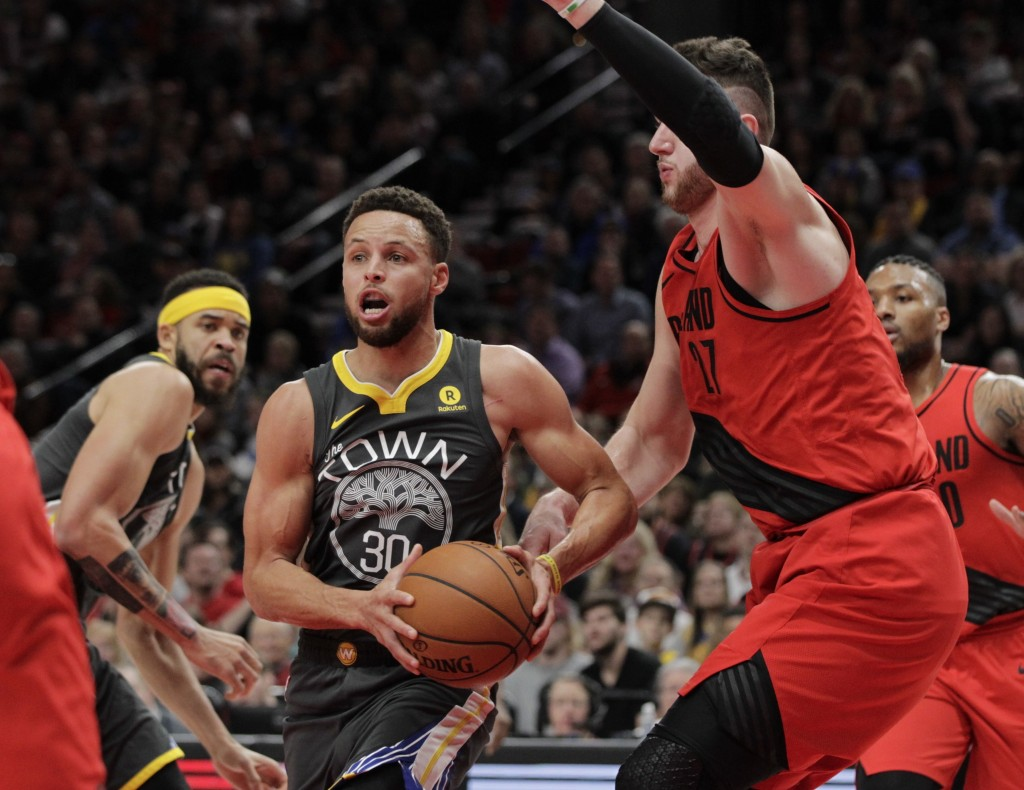 Golden State Warriors guard Stephen Curry, left, drives past Portland Trail Blazers center Jusuf Nurkic during the first half of an NBA basketball gam