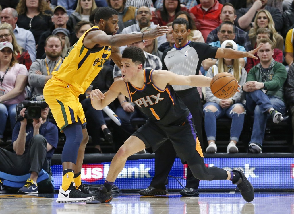 Utah Jazz forward Royce O'Neale, left, guards Phoenix Suns guard Devin Booker (1) in the first half during an NBA basketball game Wednesday, Feb. 14,