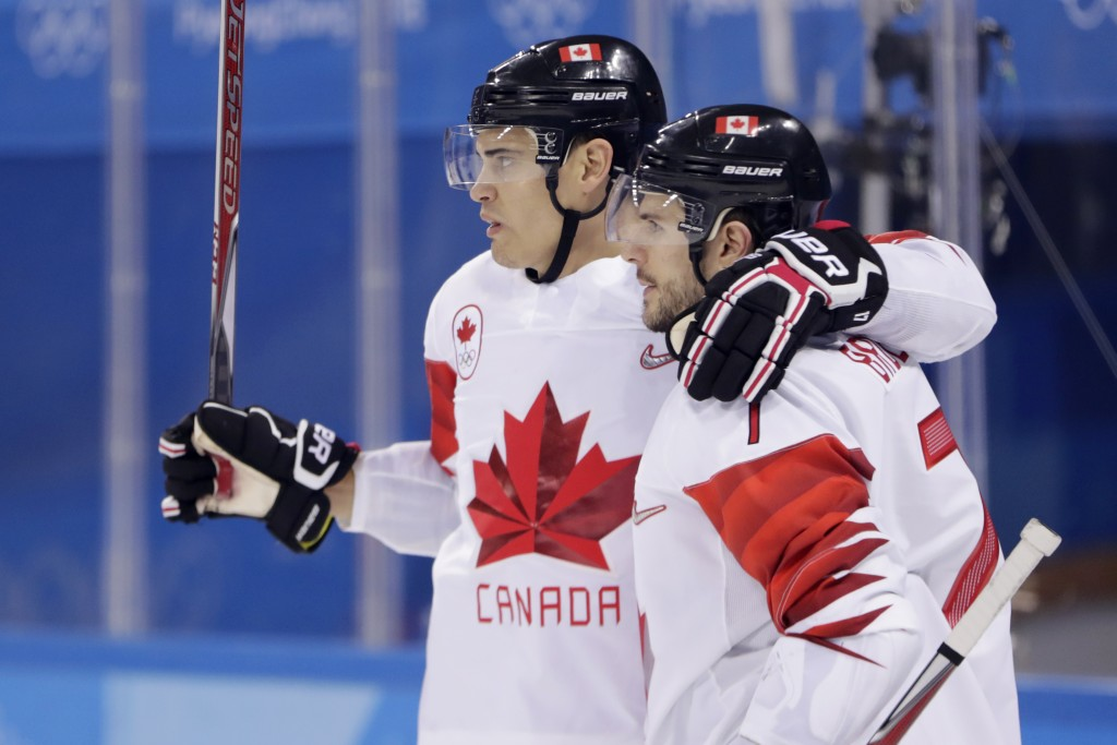 Rene Bourque, left, of Canada, celebrates his goal with teammate Gilbert Brule (7) during the second period of a preliminary round men's hockey game a