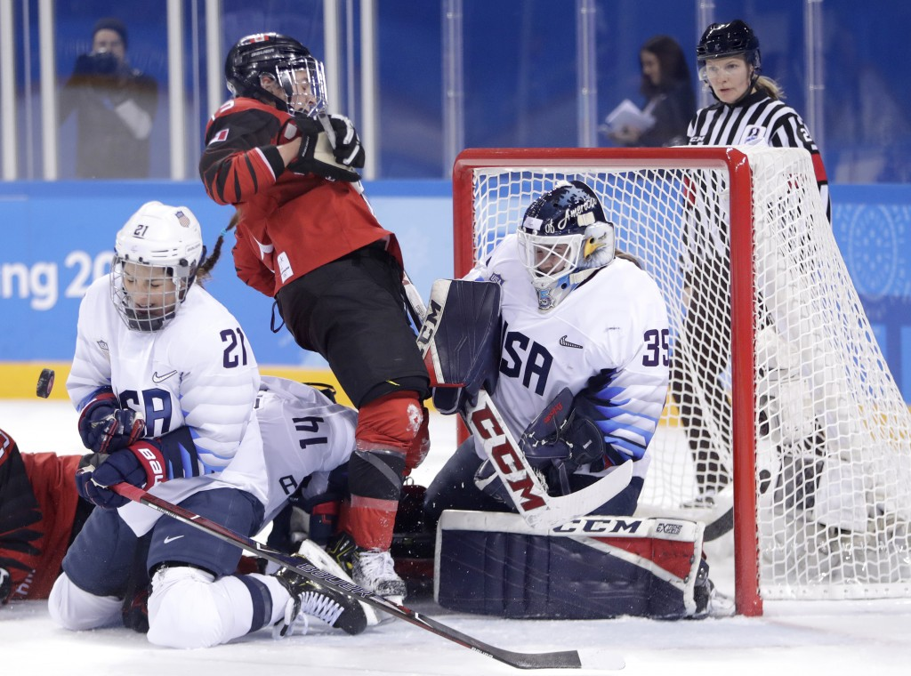 Hilary Knight, left, of the United States, blocks a shot by Canada as teammate goalie goalie Maddie Rooney, right, protects her net against Canada's M