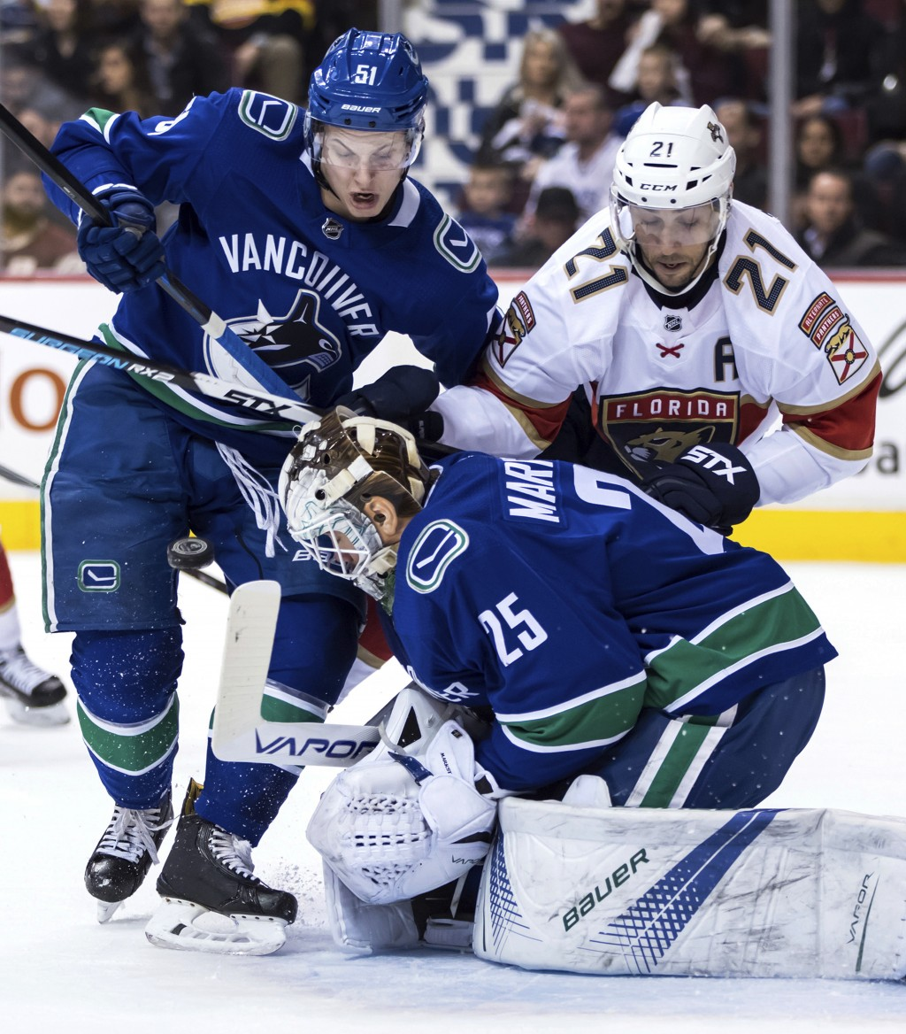 Vancouver Canucks goalie Jacob Markstrom (25), of Sweden, makes the save as Troy Stecher (51) defends against Florida Panthers' Vincent Trocheck (21)