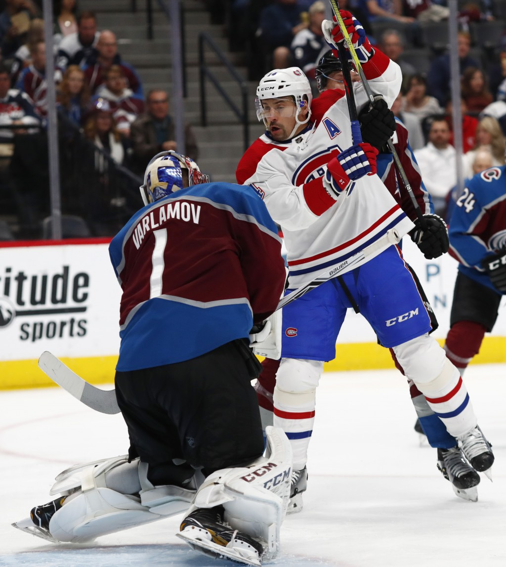 Colorado Avalanche goaltender Semyon Varlamov, left, stops a shot off the stick of Montreal Canadiens center Tomas Plekanec in the second period of an