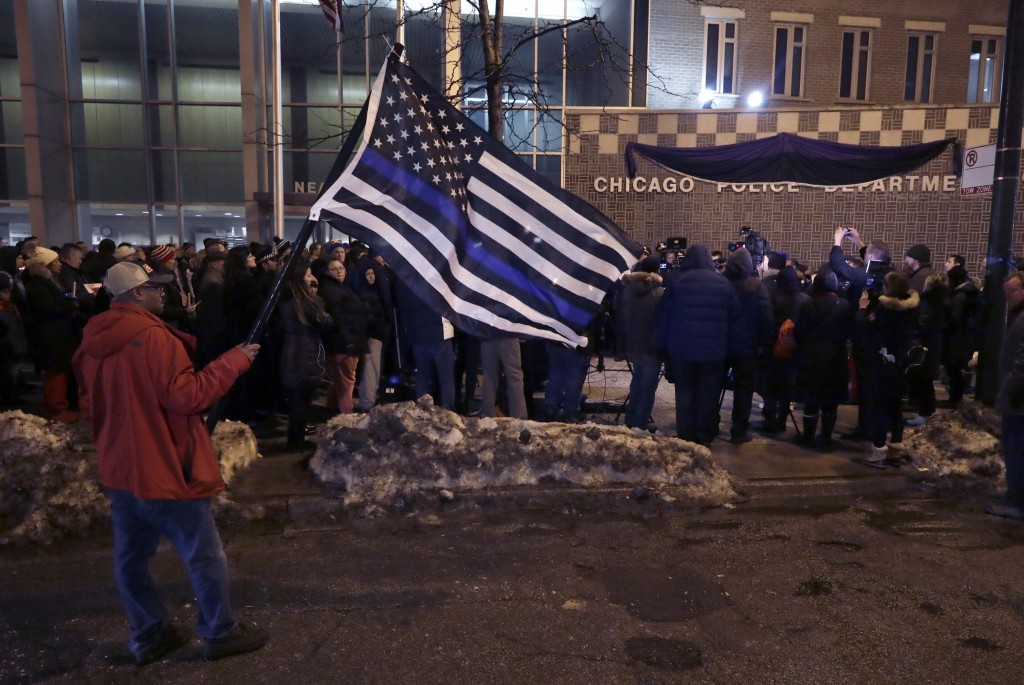 James Poole holds a police memorial American flag as he attends a candlelight vigil for Chicago Police Cmdr. Paul Bauer outside the Near North Distric