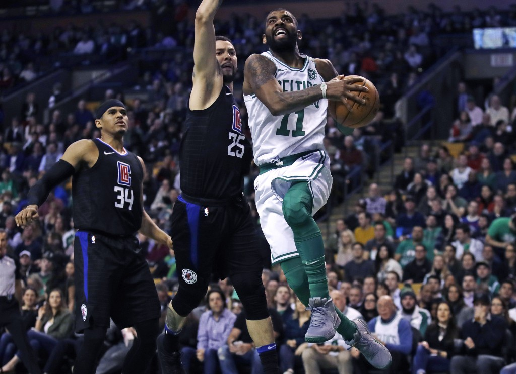 Boston Celtics guard Kyrie Irving (11) drives past Los Angeles Clippers guard Austin Rivers (25) and forward Tobias Harris (34) during the first quart