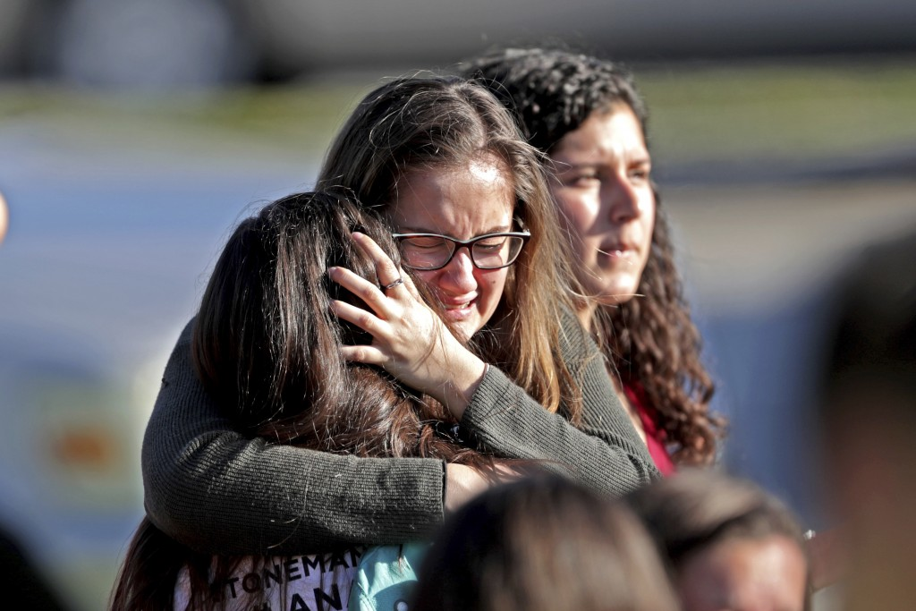 Students released from a lockdown embrace following following a shooting at Marjory Stoneman Douglas High School in Parkland, Fla., Wednesday, Feb. 14