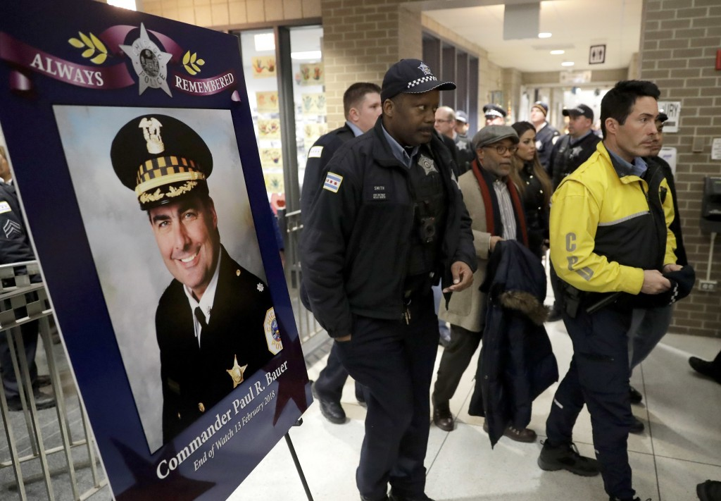 Chicago police officers pass a memorial portrait of Cmdr. Paul Bauer for a candlelight vigil for Bauer outside the Near North District headquarters We