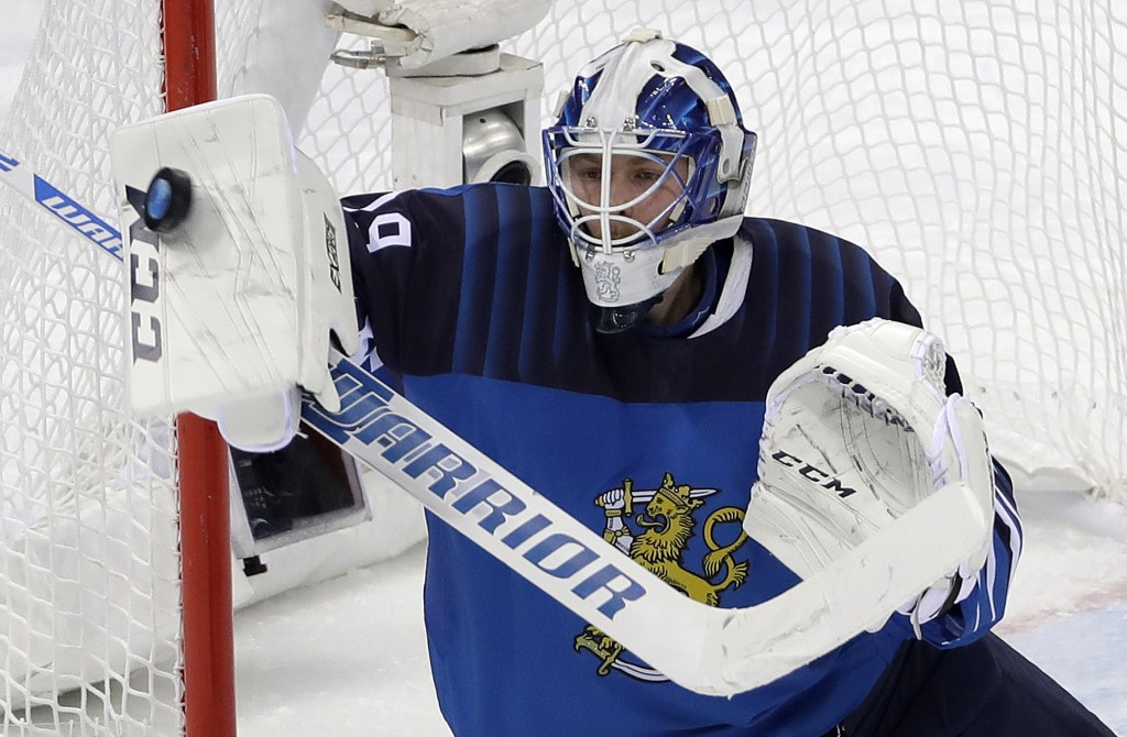 Goalie Mikko Koskinen (19), of Finland, blocks a shot during the third period of the preliminary round of the men's hockey game against Germany at the