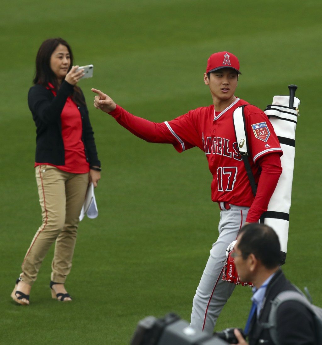Los Angeles Angels' Shohei Ohtani gestures to fans as he takes the field during a spring training baseball practice on Wednesday, Feb. 14, 2018, in Te