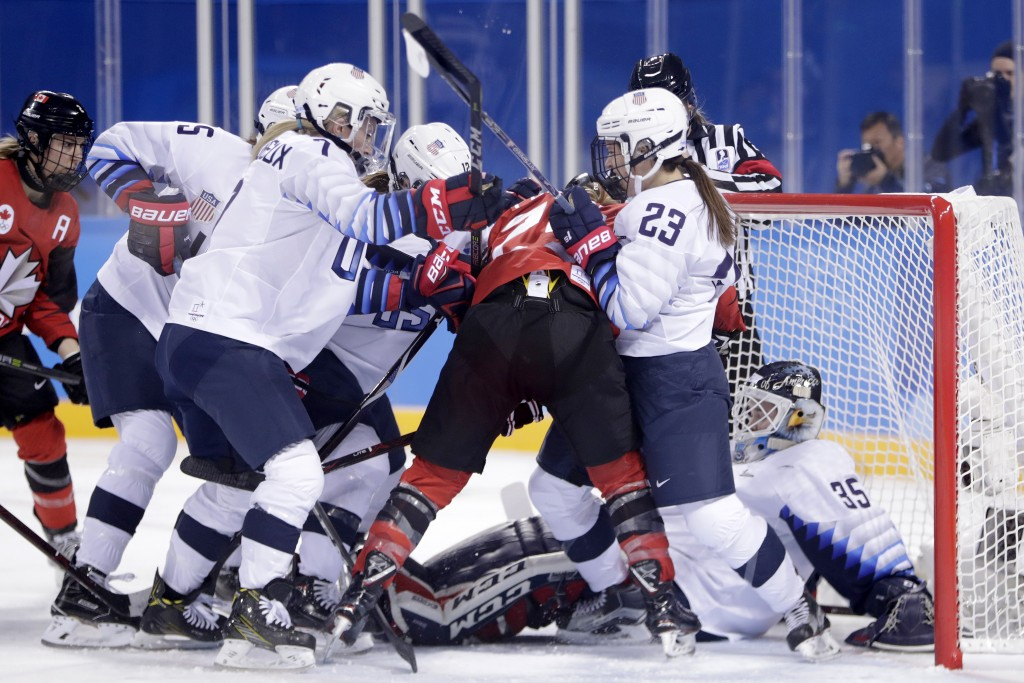 United States goalie Maddie Rooney, far right, falls into her net as teammates compete for the puck with Canada players during the first period of a p