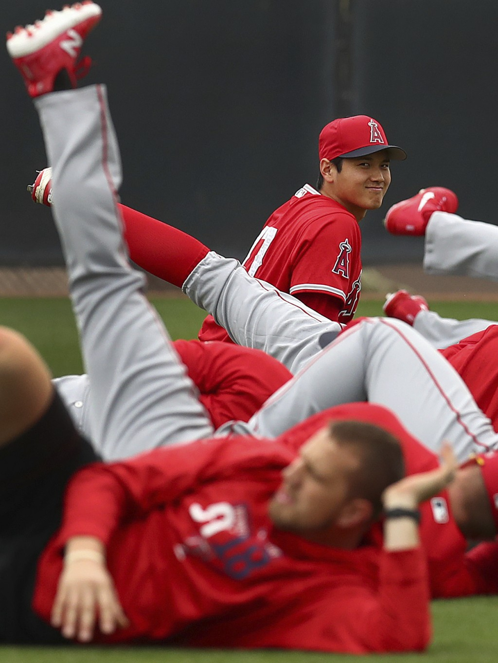 Los Angeles Angels' Shohei Ohtani smiles during a stretching exercise at a spring training baseball practice on Wednesday, Feb. 14, 2018, in Tempe, Ar