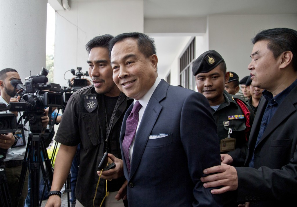 Thai former national police chief Somyot Poompanmoung, center, leaves after being interrogated at Department of Special Investigation in Bangkok, Thai