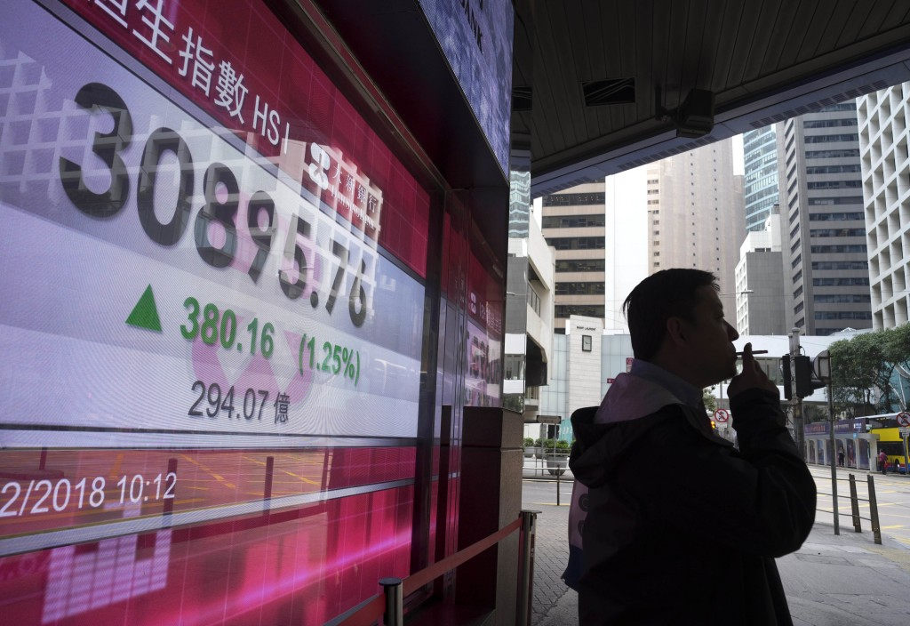 A man stands next to an electronic board showing Hong Kong share index outside a local bank in Hong Kong, Thursday, Feb. 15, 2018. Asian shares posted