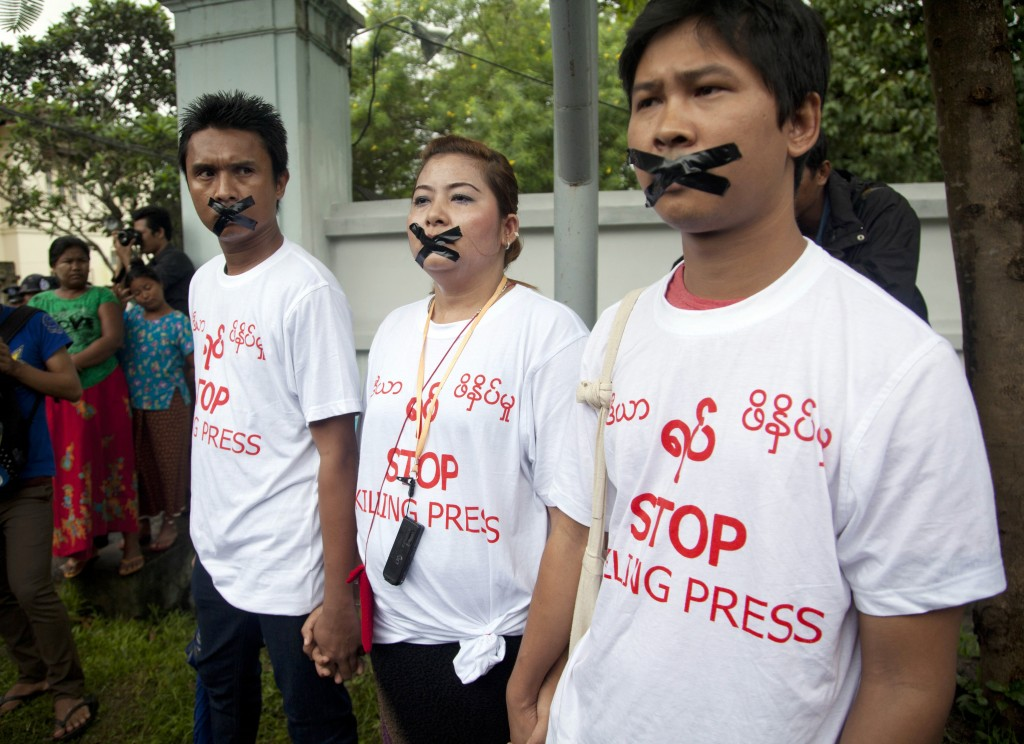 FILE - In this July 12, 2014, file photo, Myanmar journalist Thet Oo Maung, known as Wa Lone, right, stands with other journalists with their mouths t