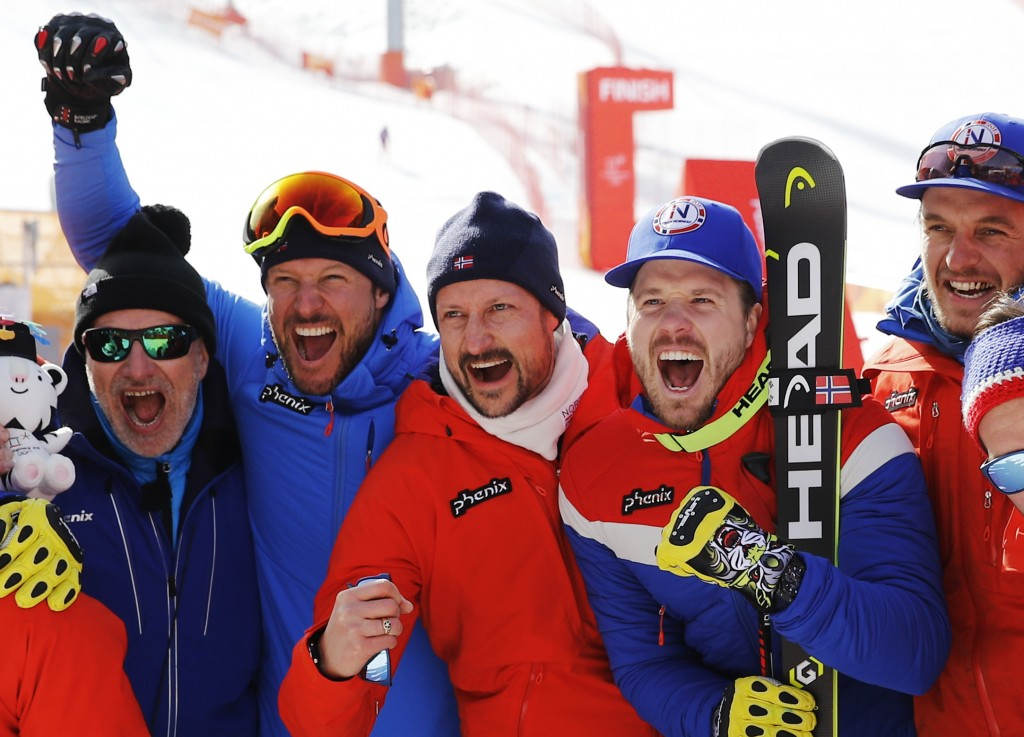 Crown Prince Haakon of Norway, center, poses for photos flanked by Norway's Aksel LundSvindal, gold, left and Norway's KjetilJansrud, silver, right,