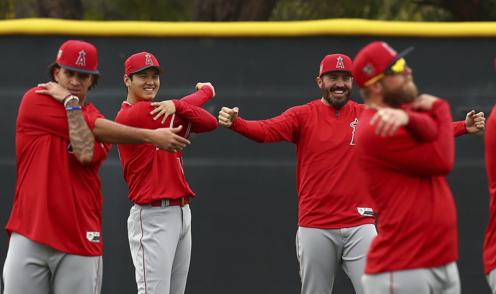Los Angeles Angels' Shohei Ohtani, second from left, smiles during a stretching exercise with other Angels pitchers at a spring training baseball prac